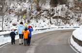 Young family with three children walking on snow-covered road in — Stock Photo