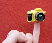 Little finger with a small toy camera — Stock Photo