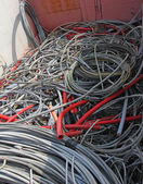 Many obsolete electrical cables and copper cables in a container — Stock Photo