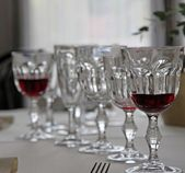 Bohemian crystal glasses lined up in set table — Stock Photo