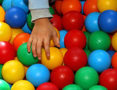 Hand of a child with a band-aid that takes the colored balls — Stock Photo