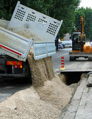 Truck tipper during the emptying of the gravel road during the e — Stock Photo