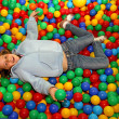 Постер, плакат: Nice little girl play dipped in colored balls of kindergarten po