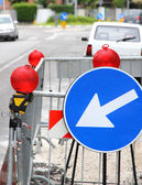 Narrowing of the roadway with red signal lamps and a road sign t — Stock Photo