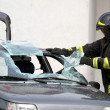 Постер, плакат: Fireman while breaking a car windshield to release the people in