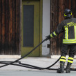 Italian fireman collects the water hose after turning off the fi — Stock Photo #47200361