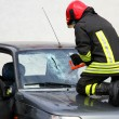 Постер, плакат: Fireman with work gloves while breaking a car windshield to rele