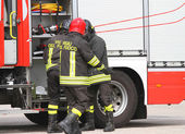Italian firefighters near fire truck by preparing to put out the — Stock Photo