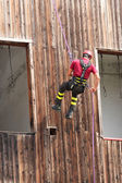 Firefighter climber down into the wall of the House in abseiling — Stock Photo