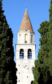 High Bell Tower of the ancient city of AQUILEIA among tall cypre — Stock Photo