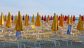 Closed umbrellas and deckchairs on the beach at sunset on the se — Stock Photo