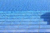 Blue steps that descend towards the big blue resort pool — Stock Photo