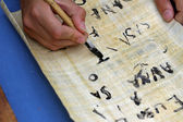 Child writing with black ink on an Egyptian Papyrus parchment — Stock Photo