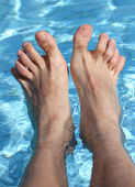 Man's feet on the bathtub of a relaxing pool — Stock Photo