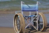 Wheelchair with stainless steel wheels to enter in to the sea — Stock Photo
