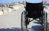 Wheelchair from behind near the shore of the sea — Stok fotoğraf
