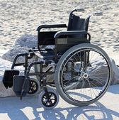 Wheelchair on the sandy beach by the sea in summer — Stok fotoğraf
