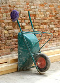 Wheelbarrow laid on the wall and worker's Cap — Stock Photo