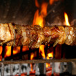Skewers of meat cooked on a spit in the fireplace 2 — Stock Photo #50296601