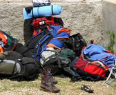 Backpacks bags and boots piled up after the long walk of the boy — Stock Photo
