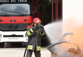 Fireman extinguishes the fire after car accident 1 — Stock fotografie