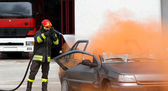 Fireman extinguishes the fire after car accident 2 — Стоковое фото