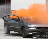 Orange smoke escapes from the car destroyed — Stock fotografie