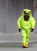 Rescuer with the yellow suit against biological hazard from cont — Stock Photo