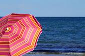 Beach umbrella on the beach and the sea — Stock Photo