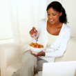 Young female having breakfast and using laptop — Stock Photo