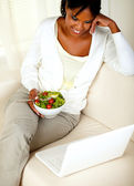 Adult black woman eating healthy green salad — Stock Photo