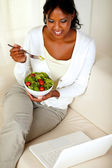 Adult woman eating healthy green salad — Stock Photo