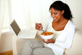 Pretty woman having breakfast and using laptop — Stock Photo