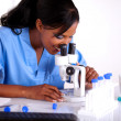 Scientific female in blue uniform using microscope — Stok fotoğraf