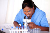 Medical doctor woman working with a microscope — Stock Photo