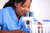 Young scientific woman using a microscope — Stock Photo
