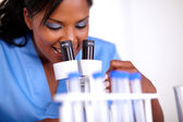 Charming medical doctor woman using a microscope — Stock Photo