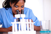 Afro-american scientific woman using a microscope — Stock Photo