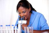 Scientific girl in blue uniform using microscope — Stock Photo