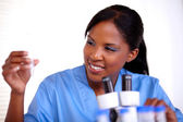 Scientific young woman looking to test tube — Stock Photo