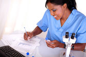 Scientific woman working with test tube and notes — Stock Photo