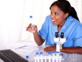 Surprised scientific female looking to test tube — Stock Photo