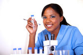 Scientific woman looking at you holding test tube — Stock Photo