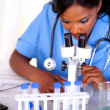 Afro-american nurse female using a microscope — Stock Photo