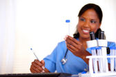 Afro-american nurse looking to test tube — Stock Photo