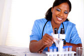 Smiling black nurse working with a test tube — Stock Photo