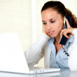 Tired young woman with headache speaking on phone — Stock Photo