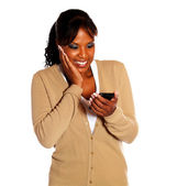 Cheerful young woman reading message on cellphone — Stock Photo