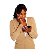 Surprised black woman reading message on cellphone — Stock Photo