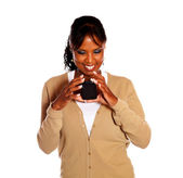 Afro-american woman reading message on cellphone — Stock Photo